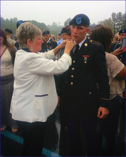 Aaron Toppen's  mother adjusts a medal at her son's Turning Blue Ceremony.